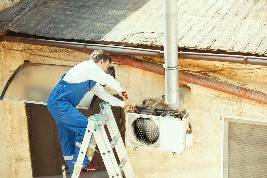Cleaning condenser unit HVAC system man