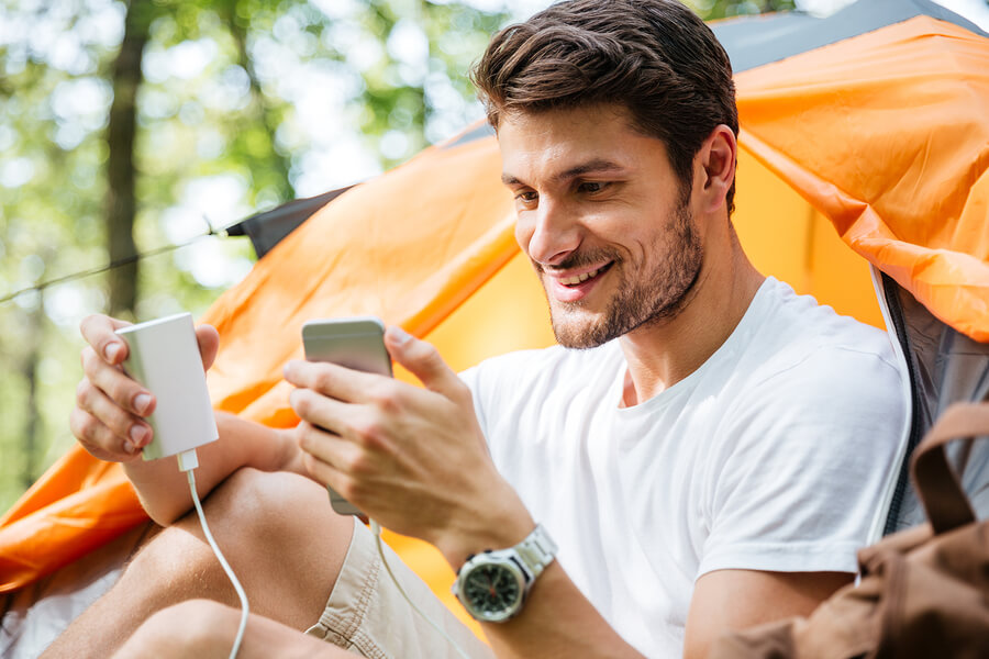 Final Rec smiling man charging phone camping tent
