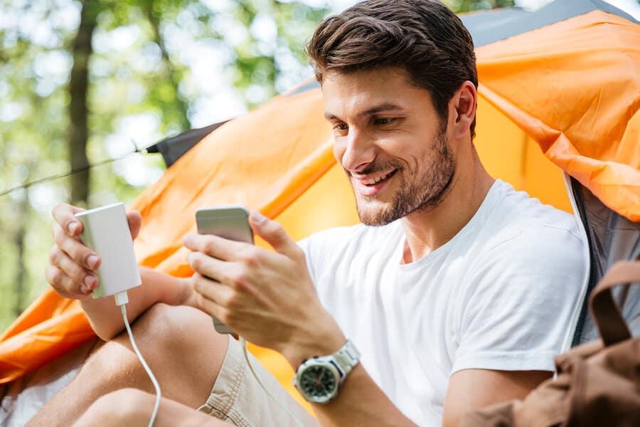 Final Rec smiling man charging phone camping tent