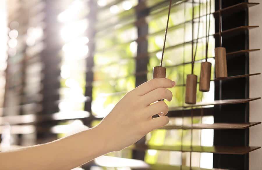 Hand closing blinds window greenery