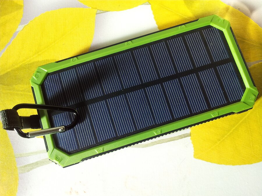 Charger Solar On Green Background With White Usb Cord For Chargi