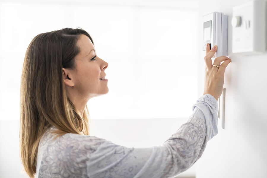 Woman adjusting thermostat smiling save money